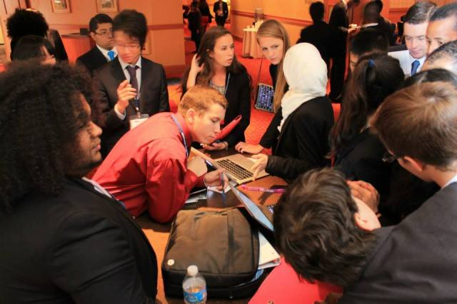 Marshal Digiovanna '16 (in red shirt) checks the progress of a working paper at the 2014 National Model UN conference in Washington DC, where he and his delegation partner, Thomas Winquist '15, won an award for an outstanding Position Paper.